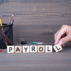 Payroll wooden letters on dark background