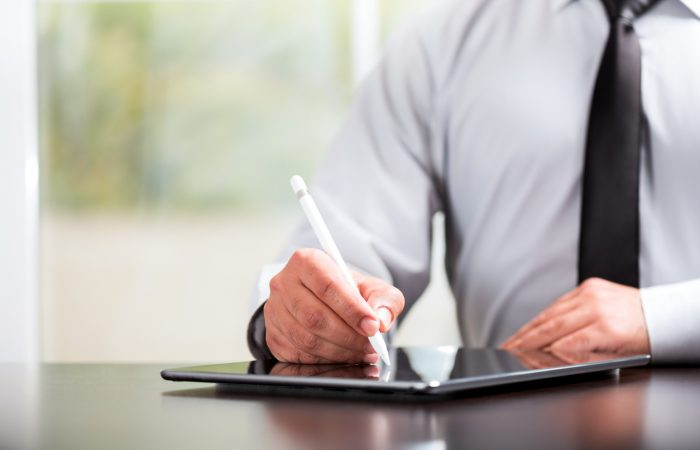 Man using e-signature technology with tablet
