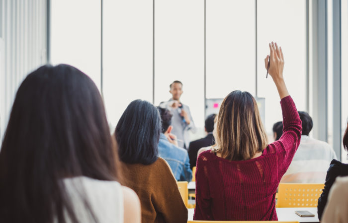 Back view business woman raising hand for asking speaker for question