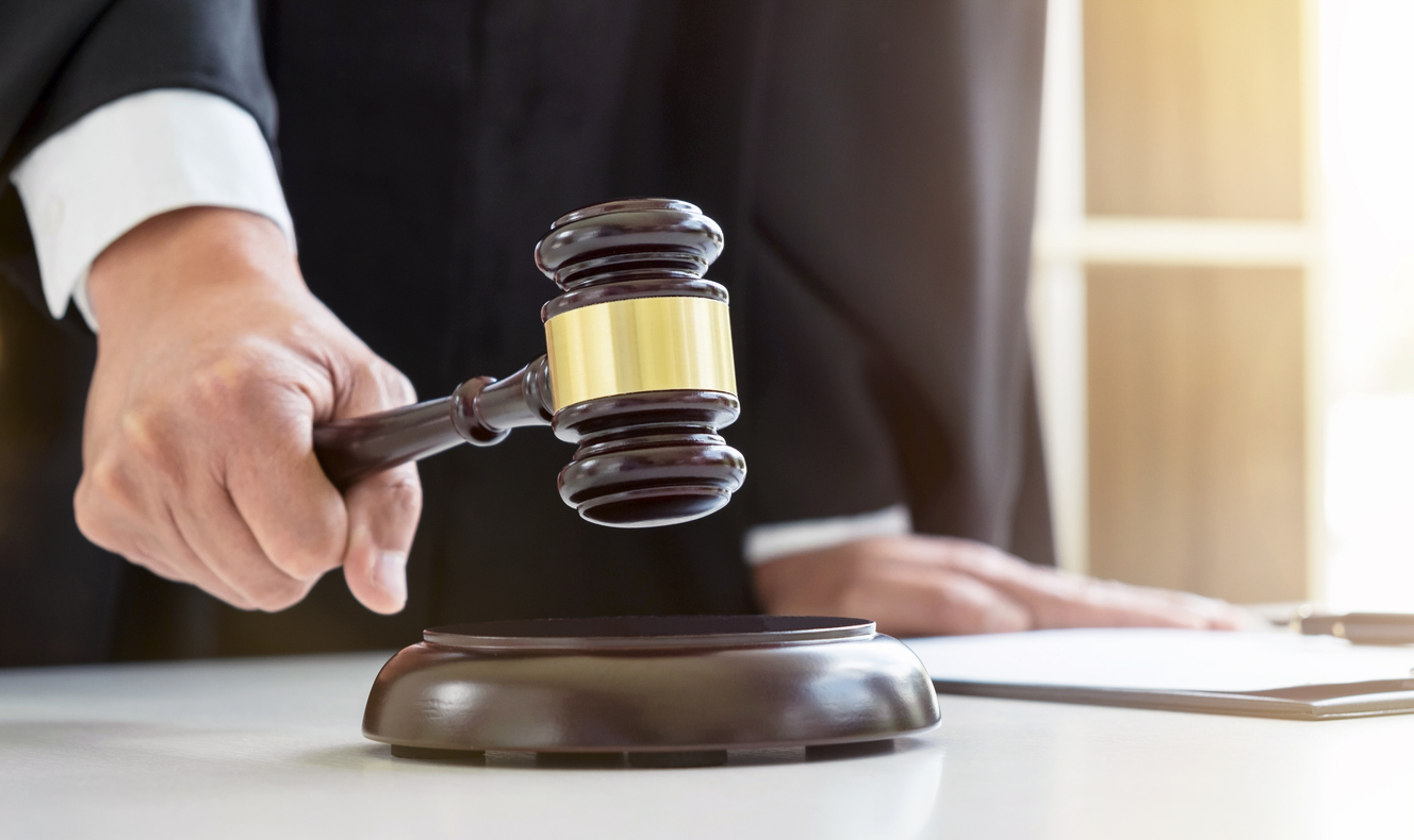 Close up of Male lawyer or judge hand's striking the gavel