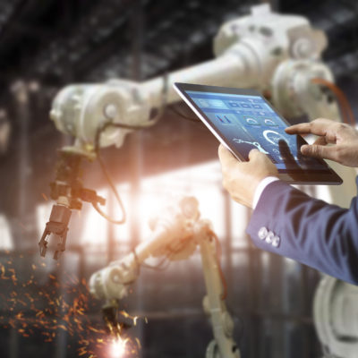 Manager industrial engineer using tablet check and control automation robot arms machin