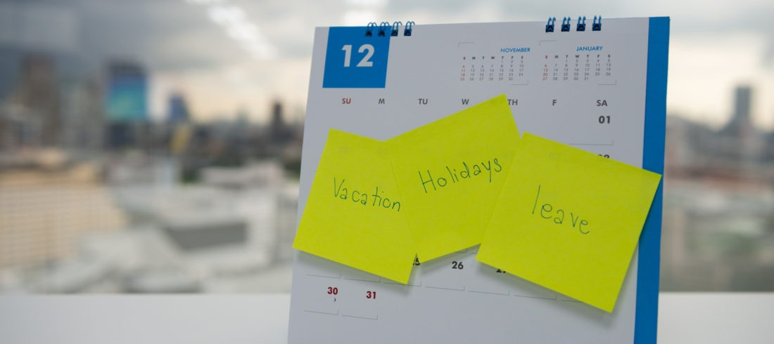 "Desk calendar with sticky notes saying ""vacation"", ""holidays"", and ""leave"""