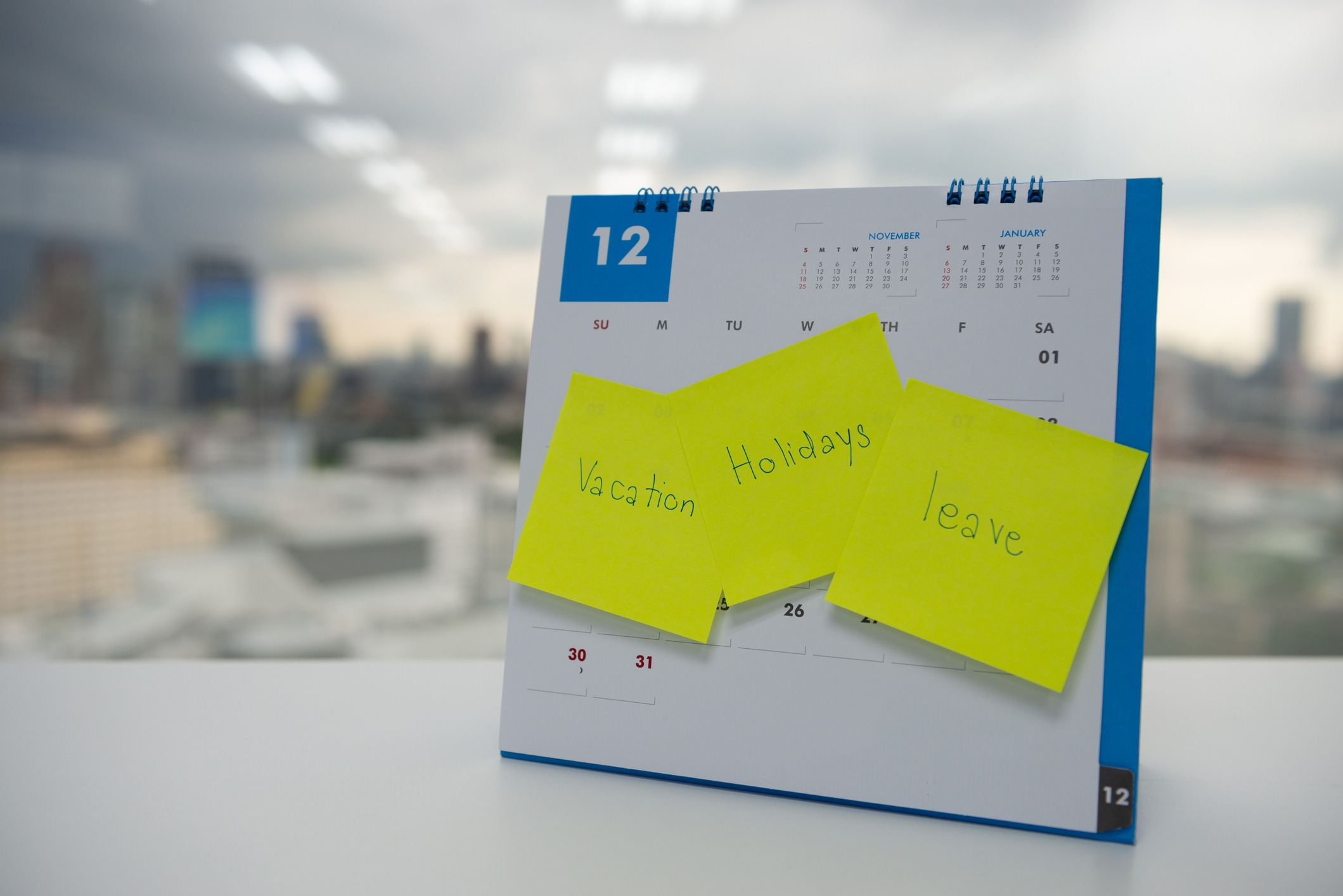 """Desk calendar with sticky notes saying """"vacation"""", """"holidays"""", and """"leave"""""""