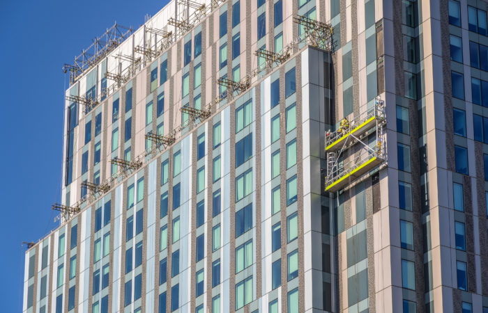 Construction workers on a building implementing cladding
