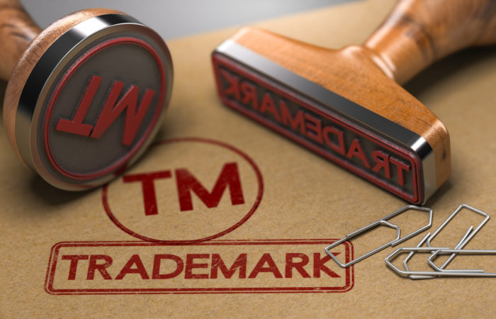 Two rubber stamps with the word trademark and the symbol TM over brown paper background