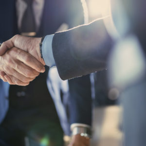 People in suits shaking hands in partnership