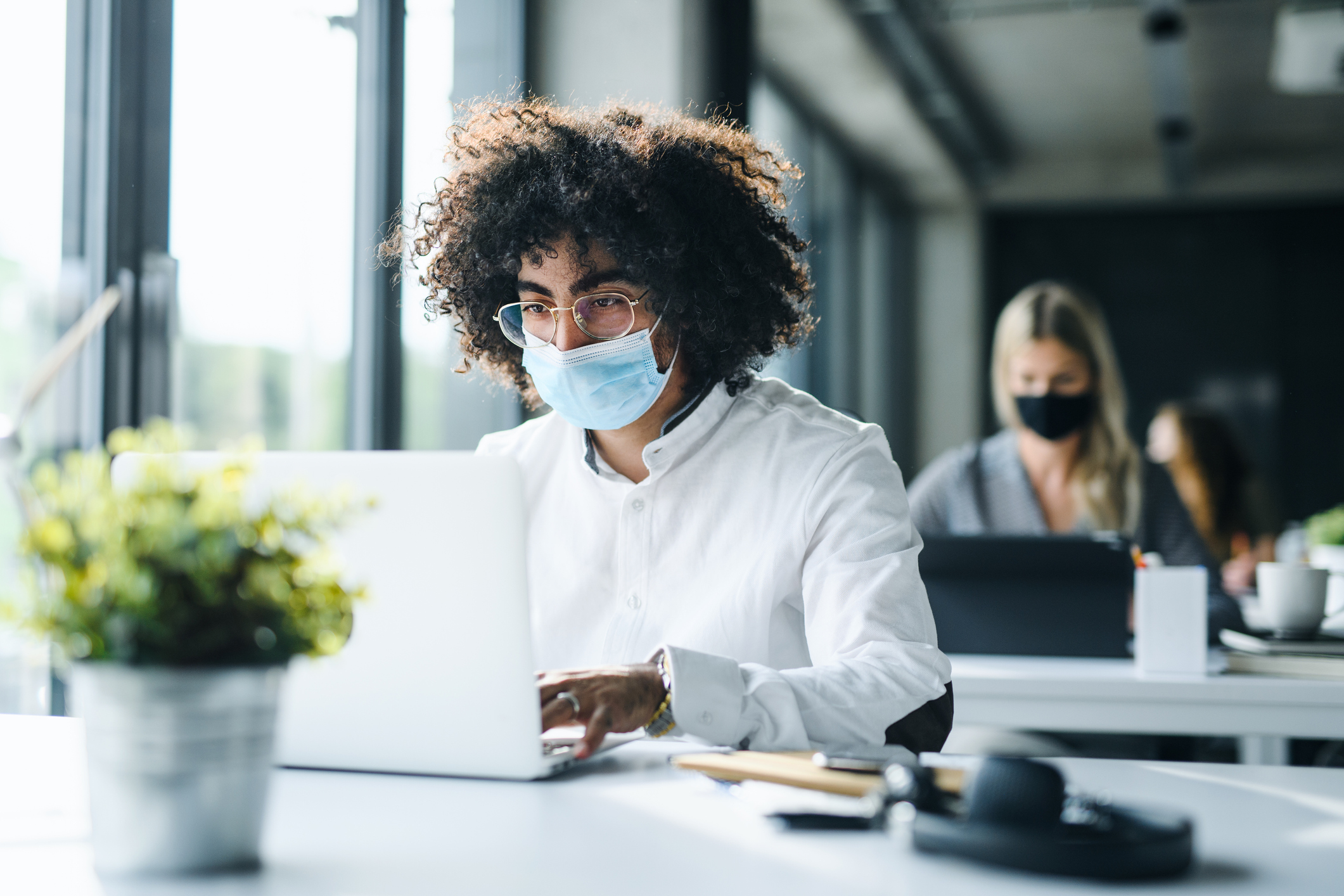 man with face mask back at work in office after lockdown, working.